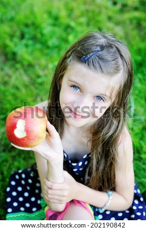 Beauty brunette kid girl eating apple outdoors in the summer day - stock photo