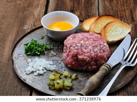 Beef tartar with egg, pickled cucumber and onion. Selective focus - stock photo