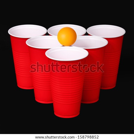 Beer pong. Red plastic cups and orange table tennis ball over black background. Closeup - stock photo
