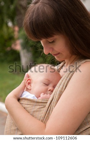 Best deep sleep. Newborn baby sleeping in a sling, in the embrace of her mother. - stock photo
