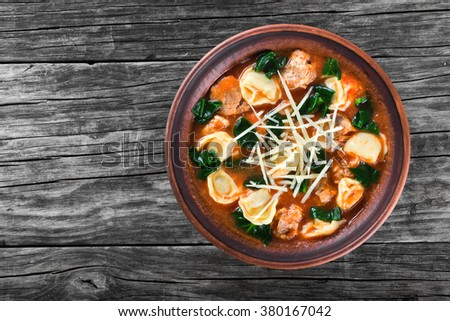 best tortellini soup with italian sausages, spinach, tomato, shredded parmesan cheese and spices in a clay rustic bowl on an old table, top view