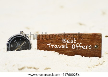 """Best Travel Offers"" text on wooden keychain with compass on the tropical white sand beach - vacation and business concept - stock photo"