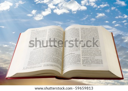 Bible in spanish floating in sky background - stock photo