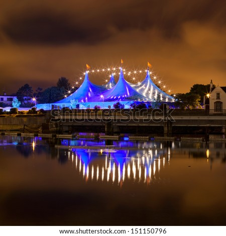 """Big Top"" circus style blue tent and row of lights on the bank of Corrib river in Galway, Ireland"