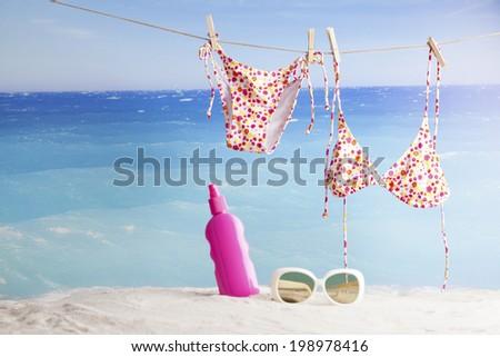 bikinis hanging on tropical beach , summer background - stock photo