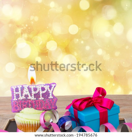 birthday cupcake with burning happy birthday candle on golden background with copy space - stock photo