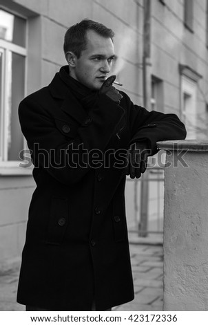 Black and white portrait of a young man with a cigarette - stock photo