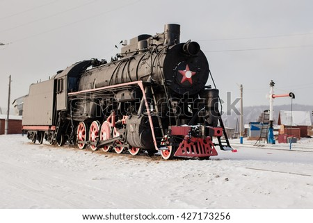 Black old steam locomotive on the winter station.  Port Baikal, Russia - stock photo