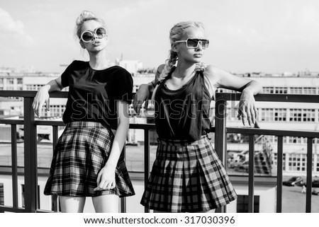 Black white portrait portrait of two pretty hipster blonde sisters  wearing plaid skirt and  black T-shirt. Girls smile, have fun against  urban city. - stock photo