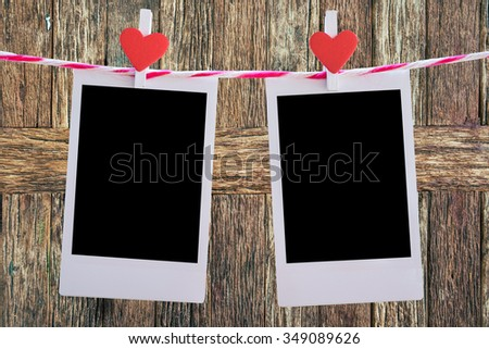 2 Blank instant photo and red clip paper heart hanging on the clothesline with old wood background.Designer concept. - stock photo