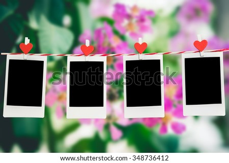 4 Blank instant photo and red clippaper heart hanging on the clothesline with pink flower nature background.Designer concept. - stock photo