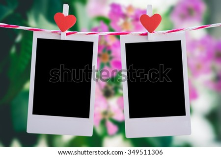 2 Blank instant photo and red clippaper heart hanging on the clothesline with pink flower nature background.Designer concept. - stock photo