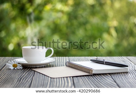 blank white notebook, pen and cup of coffee on the desk - stock photo