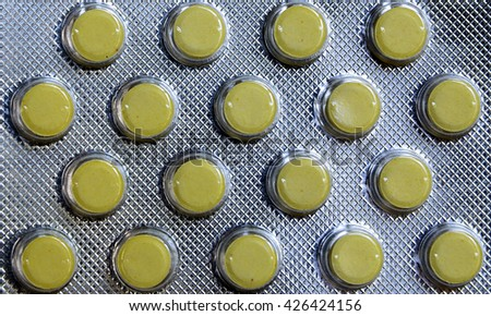 Blister pack of yellow tablets background. Pills texture. - stock photo