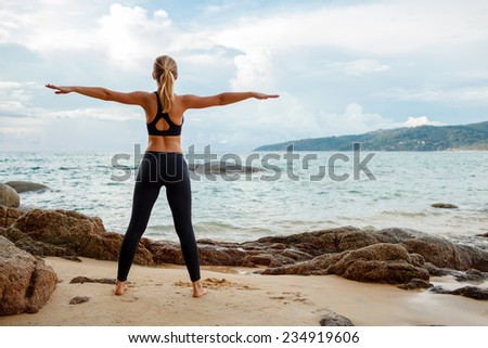 blond young women doing yoga with the ocean behind