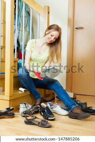 blonde girl cleaning shoes at home