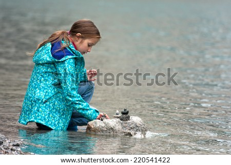 blonde girl sitting on the bank of the lake  - stock photo