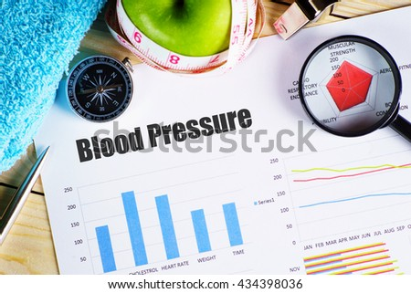 """Blood Pressure"" black text on paper with magnifying glass on red spider bar on wooden table with compass, towel, green apple with measurement tape, and whistles - fitness, diet and healthy concept - stock photo"