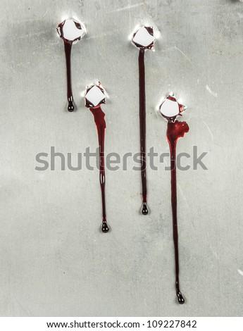 bloody gunshot holes with blood drips - stock photo
