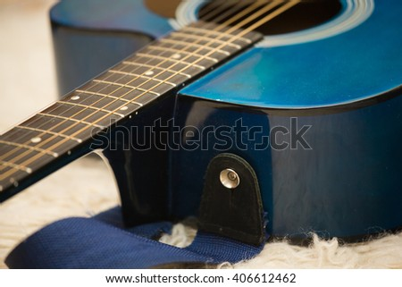 blue acoustic guitar on white carpet - stock photo