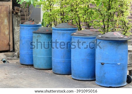 5 Blue bins with black cap placed behind house near tree pots.