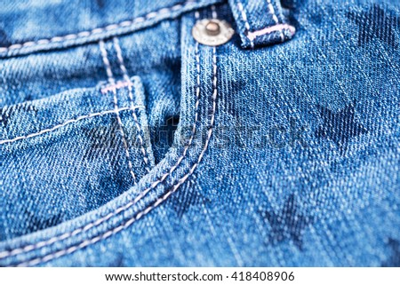 Blue jeans pockets with star print and pink thread seam, close up, top view, shallow dof - stock photo