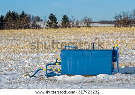 Blue Metal Capping Gas Well in Rural Winter Field - stock photo