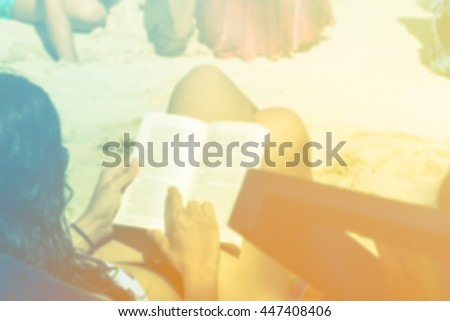 blurred background young woman reading a book while relaxing at - stock photo