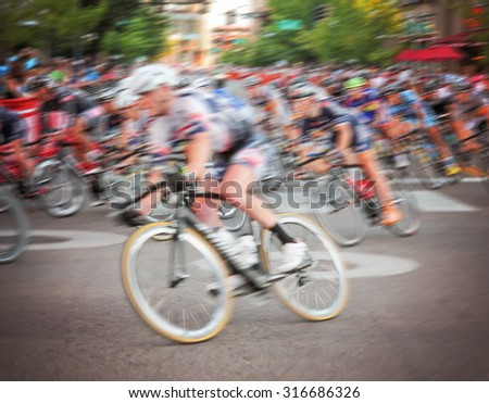 blurred image of a pack of bicycle riders rounding a corner in a bike race toned with a retro vintage instagram filter app or action effect  - stock photo