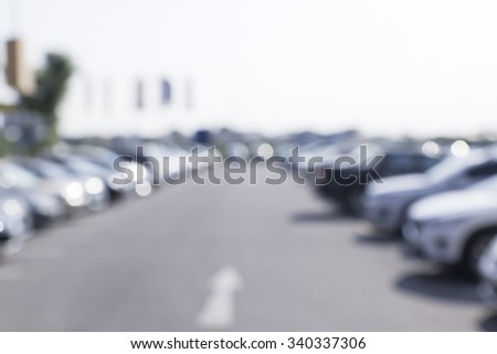 blurred image of car in outdoor parking lot at daytime - stock photo