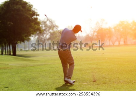 blurry golfers hit sweeping golf course in the summer on sunshine for relax time - stock photo
