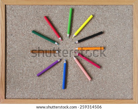 Board and colored pencils - stock photo