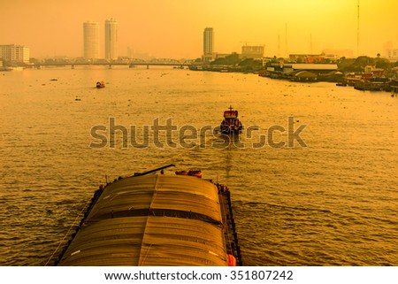 Boat pulled by a tugboat cargo carry the product at the Chaophaya river in Bangkok Thailand. - stock photo