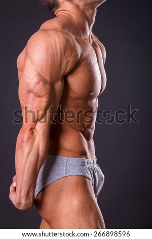 Bodybuilder posing on a black background. Muscular man showing his muscules