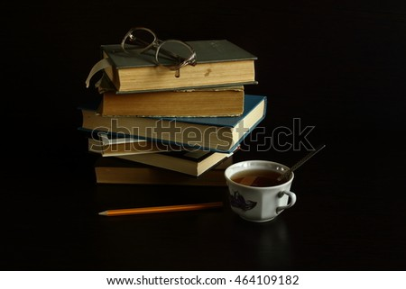 books lie on each other, near reading glasses , pencil . dark background  flour creativity and hard work