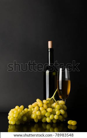 Bottle and glass of white wine with grapes against dark background - stock photo