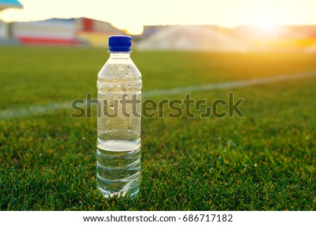 bottle of water on a green football field on a hot sunny day