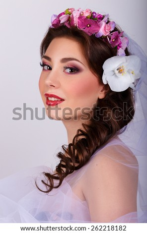 Bouquet of Beautiful Flowers on lady's head.brunette in a tulle dress. Fashion Art.Hairstyle with flowers.girl with orchids flower in her hair. Professional Make-up.Makeup.  - stock photo