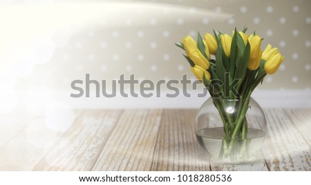 bouquet of yellow tulips in a vase on floor