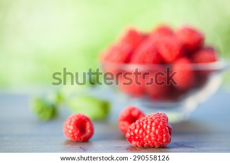Bowl of fresh organic raspberries on the wooden table. Selective focus. Natural background. - stock photo