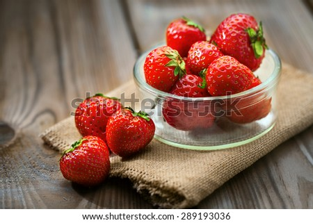 Bowl with fresh strawberries on a wooden ground - stock photo