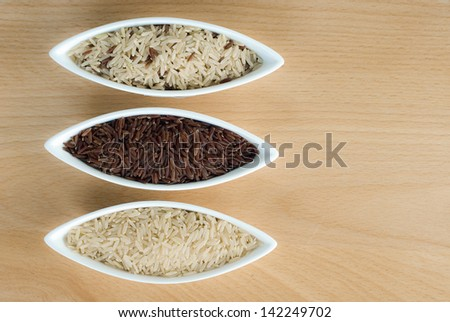3 bowls of raw rice; brown, red, and mixed rice - stock photo