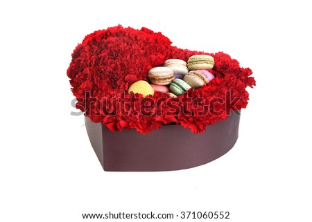 box in the form of heart, is filled by flowers and cookies.  Red carnations, white background. - stock photo