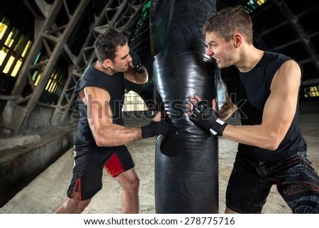 boxer man during boxing hitting heavy bag at training - stock photo