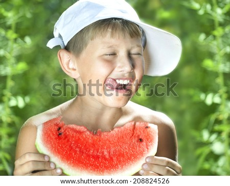boy eating a hot summer day juicy watermelon - stock photo