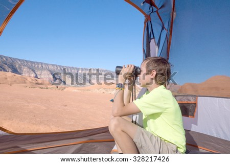 Boy looking through binoculars while sitting in a tent. Grand Staircase-Escalante National Monument, Utah - stock photo