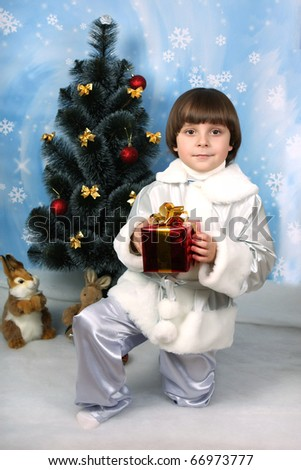 boy near a Christmas tree with gift in hand