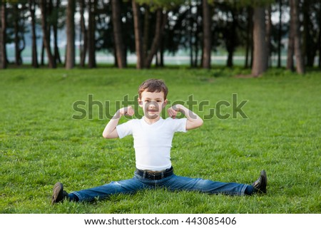 boy sitting on the splits in the park - stock photo