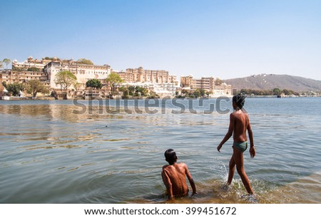 Boys are swimming in the lake Pichola, Udaipur, Rajasthan, India.Street scene - stock photo