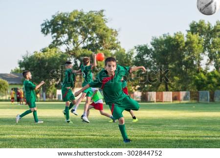 Boys kicking ball at goal - stock photo